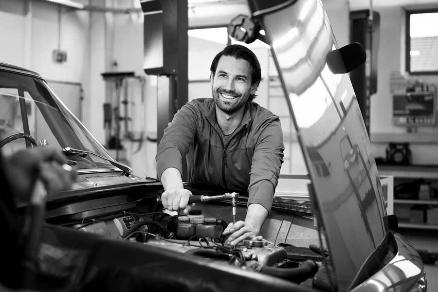 Herr Gradl schraubt an einem Motor, lächelt in die Kamera