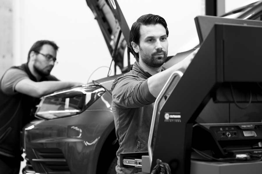 KfZ Meister Herr Gradl und ein Mitarbeiter bei der gemeinsamen Arbeit an einem Auto