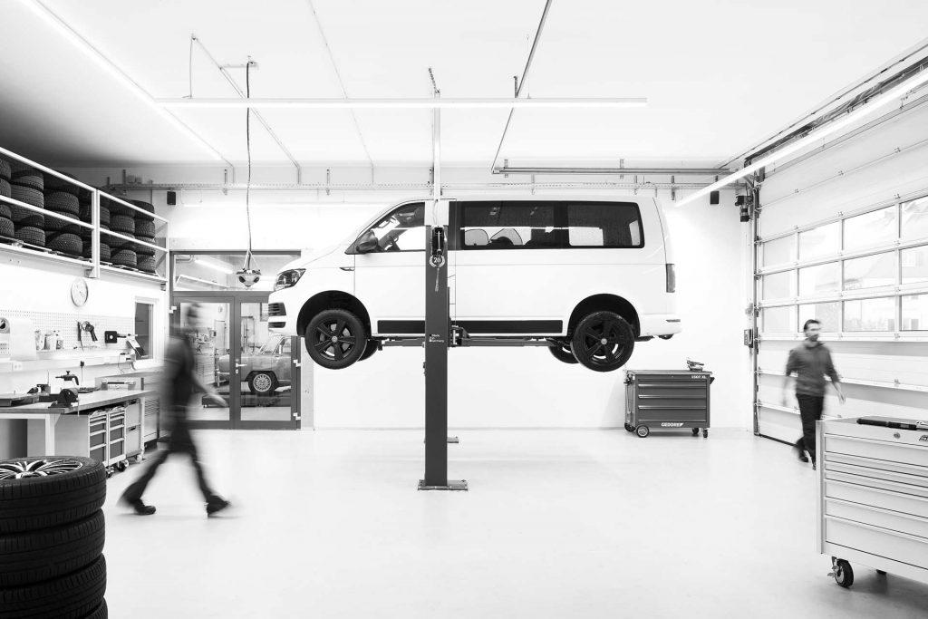 Blick in die Werkstatt von Autogradl, Minivan auf einer Hebebühne, Personen laufen durchs Bild