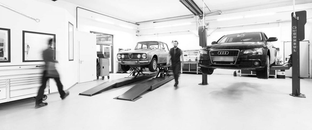Blick in die Werkstatt von Autogradl, zwei PKWs auf Hebebühnen, Personen laufen durchs Bild